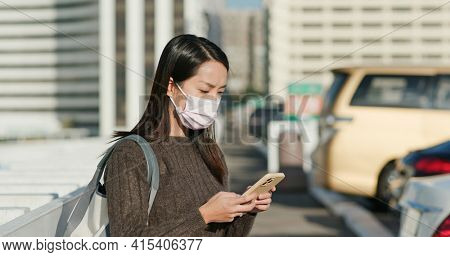 Woman wear face mask and use of smart phone to check her car on parking lot