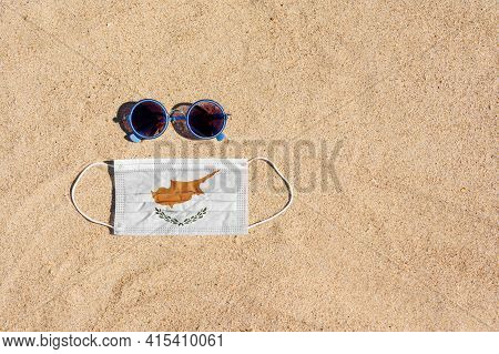 A Medical Mask In The Color Of The Cyprus Flag Lies On The Sandy Beach Next To The Glasses. The Conc