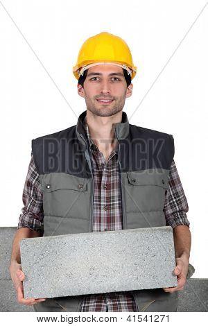 Young mason carrying a cinderblock