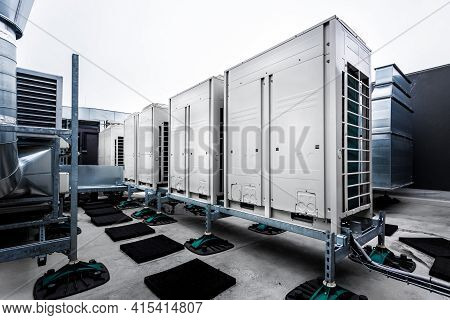 Series Of Gradually Receding Air Conditioning Units On Roof With Other Parts Of Ventilation System.