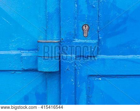 Partly Rusted Locked Industrial Blue Door With Scratched Metal Latch With Massive Lock Barrel Housin