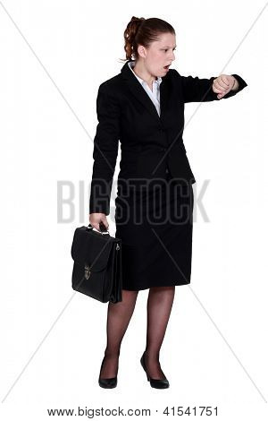 Businesswoman looking in shock at her watch