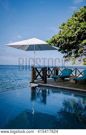 Relaxing Summer Beach , Sunbathing Deck And Private Swimming Pool With Palm Trees Near Beach And Pan