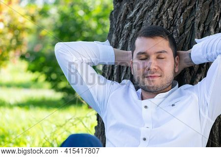 Young Man Sitting Under Tree In Park On Sunny Day. Handsome Man In Casual Wear Relaxing With Closed
