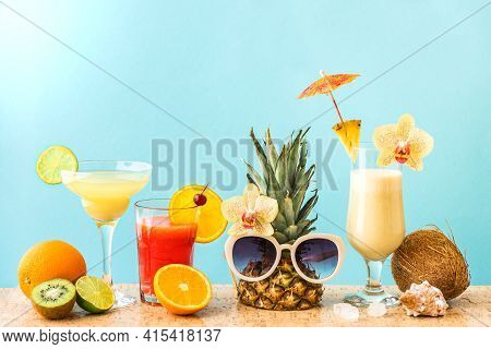 Summer Tropical Cocktail Drinks, Exotic Fruits And Flowers, Blue Background, Copy Space. Summer Vaca