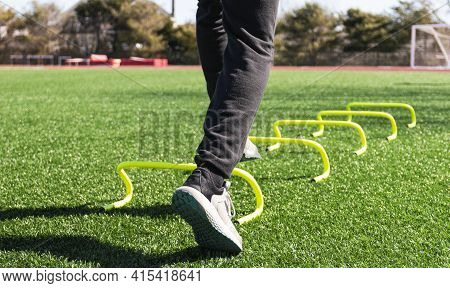 The Feet Of An Athlete Stepping Over Yellow Mini Banana Hurdles Set Up Aon A Green Turf Field For Sp