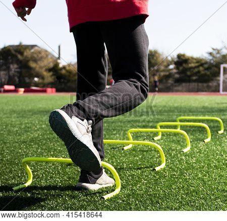 Close Up Of A High School Track Athlete Is Jumping On One Leg Over Yellow Mini Babana Hurdles On A G
