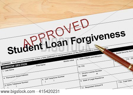 Student Loan Forgiveness Application Approved With Pen On A Wood Desk