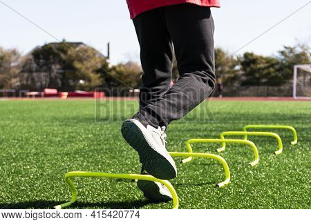 Legs Of An Athlete Jumping Over Yellow Mini Banana Hurdles On One Leg From A Low Angle View.