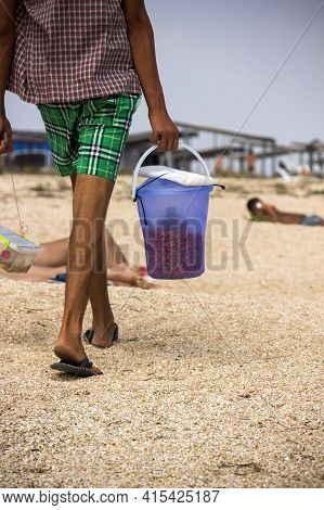 Close-up A Beach Vendor With Bucket Of Shrimps, Arabat Spit, Azov Sea, Ukraine