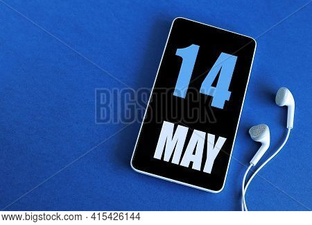 May 14. 14 St Day Of The Month, Calendar Date. Smartphone And White Headphones On A Blue Background.