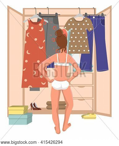 Girl In Underwear Stands In Front Of The Wardrobe And Chooses Clothes. Young Woman Trying To Choose