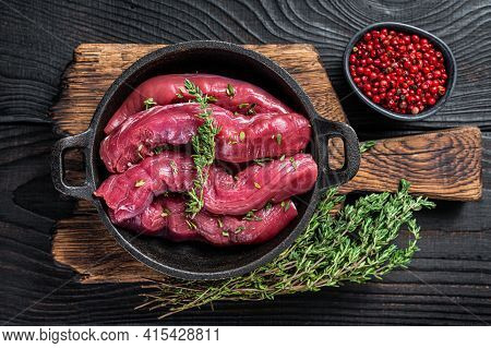 Raw Mutton Tenderloin Fillet Meat, Lamb Sirloin In Rustic Pan With Thyme. Black Wooden Background. T