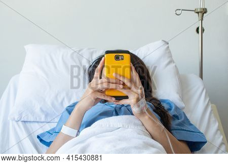 Patient Woman Lying On Bed In Hospital And Receiving Intravenous Fluid Directly Into A Vein But She