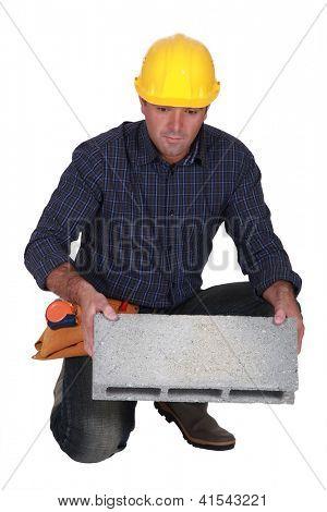 Tradesman holding a clinker block
