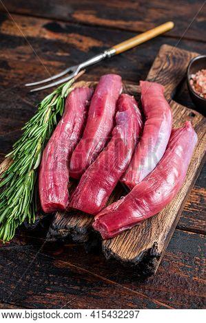 Raw Lamb Tenderloin Fillet, Mutton Sirloin Meat On Wooden Board With Herbs. Dark Wooden Background.