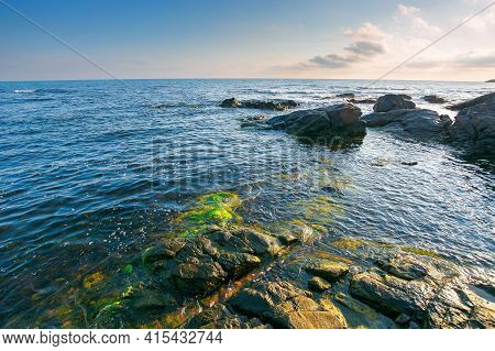 Sea Coast Scenery In The Morning. Boulders In The Calm Water. Few Clouds On The Sky In Forenoon Ligh