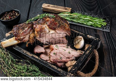 Roasted Mutton Lamb Leg Sliced In A Wooden Tray With Meat Cleaver. Black Wooden Background. Top View