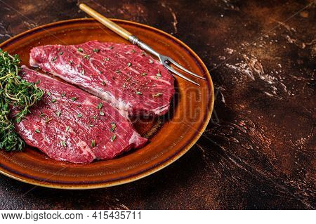 Raw Rump Cap Steak Or Top Sirloin Steak In Rustic Plate With Thyme And Olive Oil. Dark Background. T