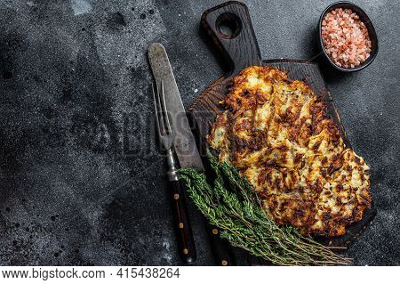 Potato Pancakes With Herbs And Salt On Wooden Board. Black Background. Top View. Copy Space