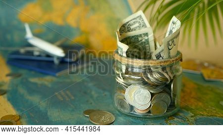 Travel Budget Concept. Money Saved For Vacation In Glass Jar With World Map, Passport And Plane. Ban
