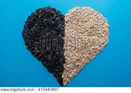 A Pile Of Watermelon Seeds On A Blue Background In The Shape Of A Heart