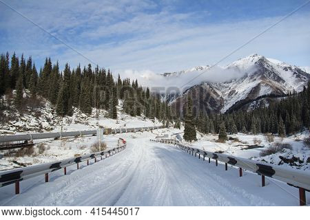 Winter Snow-covered Road High In The Mountains, Christmas Trees Grow On The Slopes Of The Mountains,