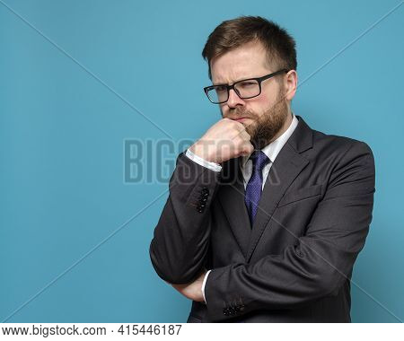 , Pensive Business Man In A Suit And Glasses Looks Sternly, Holding Hand To His Face. Copy Space. Bl