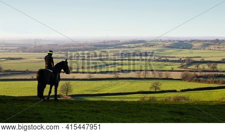 Aylesbury, Uk - December 13, 2014. Woman Riding Horse In Landscape, Horseback Riding On A Hill Overl