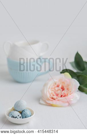 Painted Quail Eggs In A Small White Plate On A White Table. Blue And White Tea Cups And A Pink Flowe