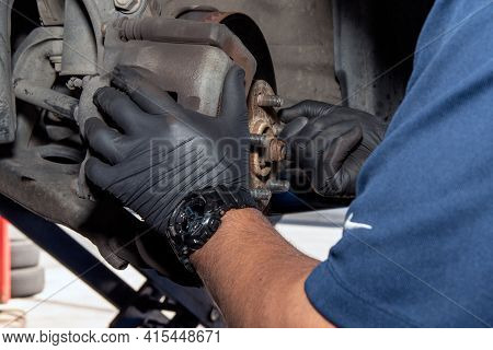 Gloved Hands Of The Mechanic Grasps A Threaded Lug On The Vehicle Wheel During A Routine Brake Inspe