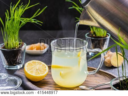Ginger Tea With Lemon In A Glass Mug On A Dark Concrete Background.