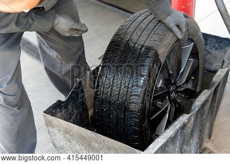 Gloved Hands Of Mechanic Performs Leak Detection On Tire By Dunking In Water In Search Of Leaking Ai