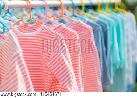 Baby Clothing On A Clothesline. Dry Clothes In Bright Colors In The Sun. Clothesline With Hanging Ba