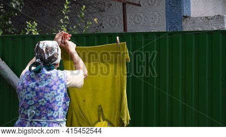 80s Old Great-grandmother With Traditional Head Scarf On Head Stand Back And Hanging Wet Laundry Wit