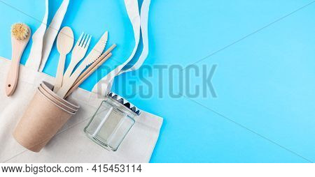 Zero Waste Or Plastic Free Concept, Wooden And Paper Utensil, Reusable Bag And Glas, On A Blue Backg