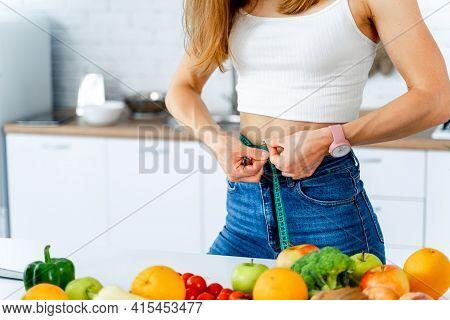 Pretty Athletic Woman Measuring Her Waist. Healthy Slim Lady Measuring Her Waistline.