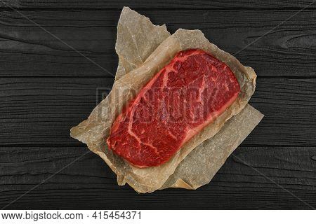 Close Up One Aged Prime Marbled Raw Sirloin Beef Steak On Brown Paper Parchment Wrapping Over Black