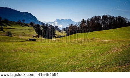 Landscape Scene With Agriculture Field, Trees, Snow Covered Mountains And Sky. Switzerland. Tranquil