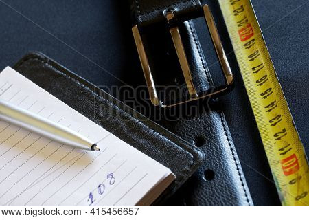 A Black Leather Belt With A Metal Buckle Rests On A Gray Background Next To A Notebook, Yellow Tape