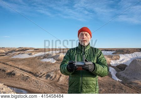 senior male drone pilot with a radio controller in a rugged terrain of Pawnee National Grassland in northern Colorado, early spring scenery