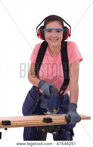 Woman using an electric jigsaw