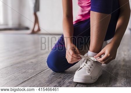 Low Section Girl Tying Shoelace White Shoes. High Quality And Resolution Beautiful Photo Concept