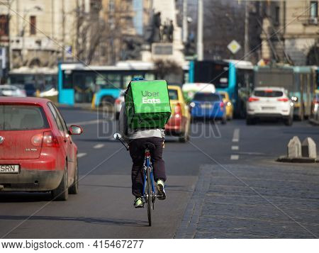 Bucharest, Romania - February 24, 2021: An Uber Eats Food Delivery Courier Delivers Food In Buchares