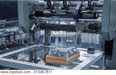 Shrink Film Wrapping Machine. Wraping Packaging Of Jars. Food Industry