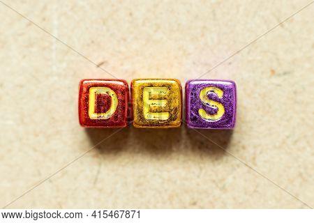 Metallic Color Alphabet Letter Block In Word Des (abbreviation Of Delivered Ex Ship) On Wood Backgro