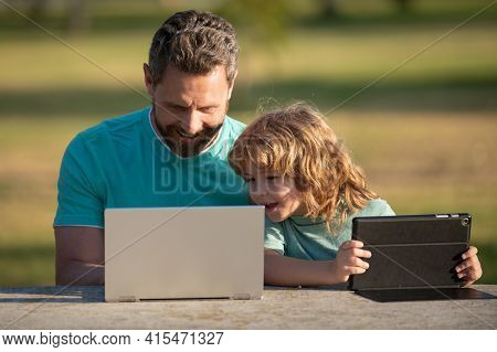 Happy Father Using Laptop Relax With Schooler Son Holding Laptop Have Fun Together, Smiling Dad And