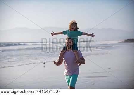 Father Giving Son Ride On Back Outside. Little Boy Kid With Daddy Carrying Him On Shoulders. Dad And