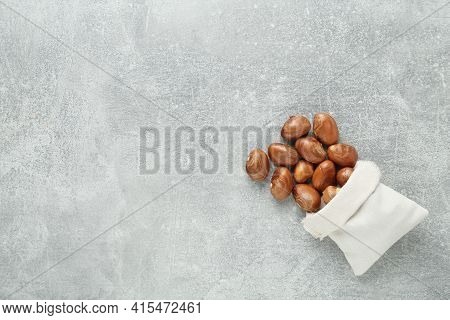 Overturned Sackcloth Bag With Jackfruit Seeds On Light Grey Table, Flat Lay. Space For Text