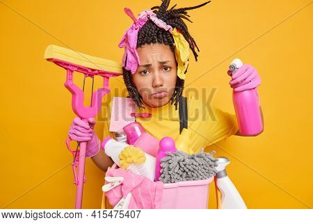 Upset African American Woman With Dreadlocks Does Cleaning Unwillingly Holds Srpray Detergent And Mo